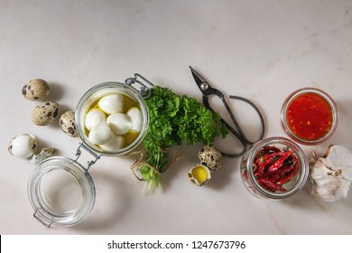 Ingredients for homemade pickled marinated quail eggs. Boiled eggs in olive oil, tomato sauce, chili peppers in jars, fresh parsley, scissors over white marble background. Flat lay, space