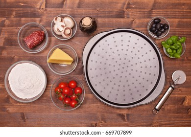Ingredients of a homemade pizza gathered on a table - top view