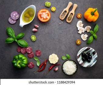 The ingredients for homemade pizza on dark stone background.