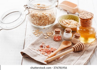 Ingredients for homemade scrub with honey, oats and Himalayan salt over white wooden background