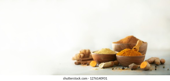 Ingredients for hot ayurvedic drink. Turmeric powder, curcuma root, cinnamon, ginger, lemon over grey background. Copy space, square crop. Spices for alternative medicine.