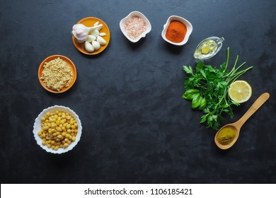 Ingredients for hummus on the black kitchen table. Top view