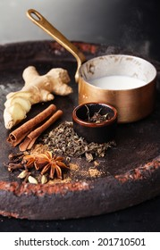 Ingredients for Indian masala tea on dark background