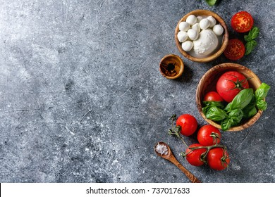 Ingredients for italian caprese salad. Mozzarella balls, buffalo, tomatoes, basil leaves, olive oil with vinegar, salt in olive wood bowls over gray texture background. Top view with copy space