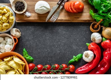 Ingredients for Italian food. Fresh vegetables, mozzarella cheese, herbs and pasta on dark stone background.
