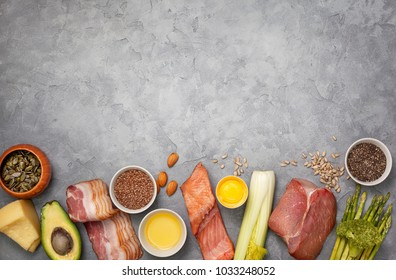 Ingredients for ketogenic diet: meat, bacon, fish, broccoli, asparagus, avocado, mushrooms, cheese, sunflower seeds, chia seeds, pumpkin seeds, flax seeds. view from above. copy space