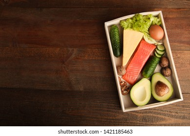 Ingredients for ketogenic diet in tray on wooden background. Concept healthy eating. Top view, copy space.