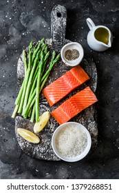 Ingredients for lunch - fresh raw organic salmon, green asparagus and rice on a dark background, top view
