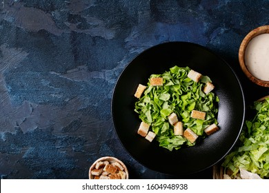 Ingredients for making classic caesar salad: chicken brests, lettuce, salt, cheese, sauce and black pepper over blue texture background. Top view, flat lay. Copy space