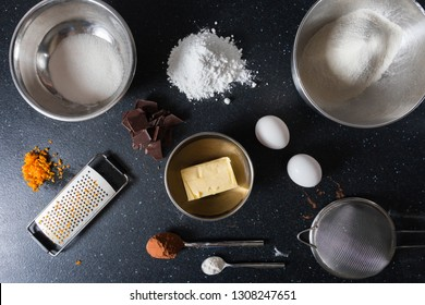 Ingredients for making creamy chocolate biscuits with cracks and dusted with icing sugar. View from above