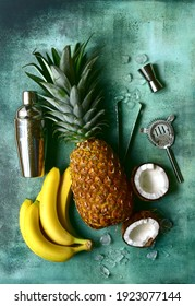 Ingredients for making delicious tropical cocktail pina colada : pineapple, coconut, banana on a green slate, stone or concrete background. Top view with copy space.
