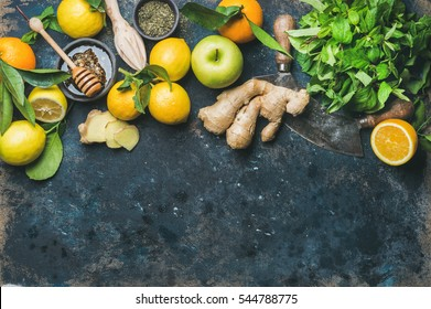 Ingredients for making flu fighting natural hot drink. Oranges, mint, lemons, ginger, honey, apple and spices over plywood background, top view, copy space. Clean eating, detox, dieting concept