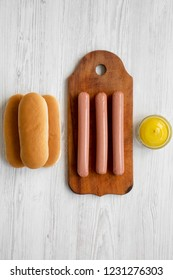 Ingredients for making hotdogs: sausages on wooden board, hot-dog buns and mustard on white wooden table, top view. Flat lay, overhead, from above.