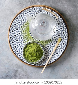 Ingredients for making matcha drink. Green tea matcha powder in ceramic bowl, bamboo spoon on decorative plate, glass teapot over grey texture background. Flat lay, space. Square image