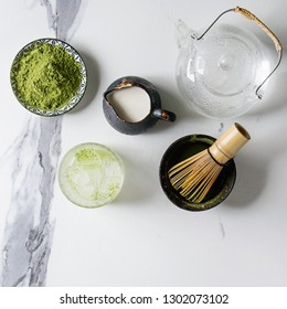Ingredients for making matcha ice drink. Green tea matcha powder in ceramic bowl, bamboo spoon, whisk, milk, glass teapot, ice cubes over white marble background. Flat lay, space. Square image