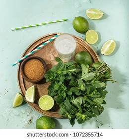 Ingredients for making mojito cocktail. Fresh mint, limes, brown sugar, crashed ice cubes, glass of soda water, cocktail tubes on wooden board over green pin up background. Top view. Square image