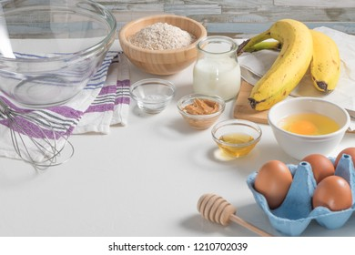 Ingredients for making pancake dough (eggs, oats flour, yogurt, banana, peanut butter, honey) on white wooden table.
