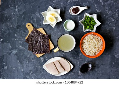 Ingredients for making ramen soup on a dark concrete background: prepared ramen noodles, pork, miso paste, soy sauce, broth, chopped green onions, boiled egg, sugar, nori seaweed. Japanese food.