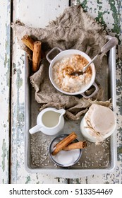 Ingredients for making rice pudding. Uncooked rice, sugar, cinnamon sticks, milk, jug of cream and pot of cooking pudding on aluminum tray over white wooden background. Top view