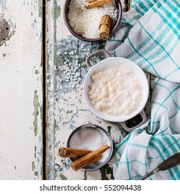 Ingredients for making rice pudding. Uncooked rice, sugar, cinnamon sticks, milk, jug of cream and pot of cooking pudding on kitchen towel over white wooden background. Top view. Square image