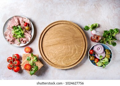 Ingredients for making sandwiches. Sliced beef meat, rye whole graine bread, green salad, tomatoes, pickled cucumber, onion on plates, empty wooden tray over grey texture background. Top view, space.