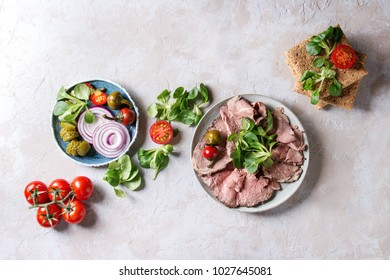 Ingredients for making sandwiches. Sliced beef meat, rye whole graine bread, green salad, tomatoes, pickled cucumber, onion on blue plates over grey texture background. Top view, space.