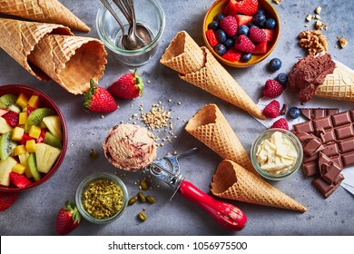 Ingredients for making and serving gourmet artisanal ice cream with fresh fruit salad and berries, chocolate, nuts, sugar cones, tubs, and a metal scoop scattered on slate in an overhead view