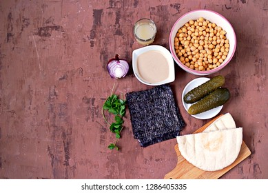 Ingredients for making snacks of chickpeas, hummus with nori seaweed and pickled cucumbers: boiled chickpeas, tahini sesame paste, nori, lemon juice, red onion, parsley and pita bread for serving.