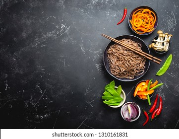 Ingredients for making stir-fried noodles soba. Cut fresh vegetables, mushrooms, boiled soba noodles in bowl with chopsticks ready for cooking, black stone background, space for text, top view