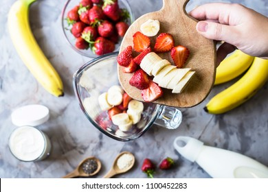 Ingredients for making strawberry banana smoothies on a gray table next to a glass bowl of blendet. Cooking a healthy breakfast concept. TOp view, flat lay