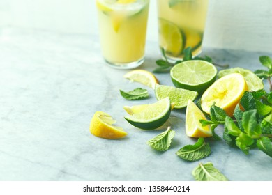 Ingredients for making a summer lemonade; lime and lemon, fresh mint leaves. Close-up