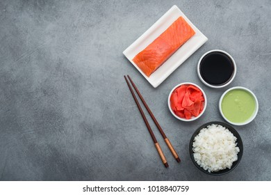 Ingredients for making sushi at home, salmon fish, wasabi, ginger, chopsticks and rice on a stone table