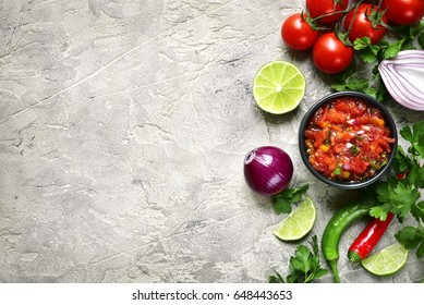 Ingredients for making tomato salsa (salsa roja) - traditional mexican sauce on a grey slate,stone or concrete background.Top view with copy space.