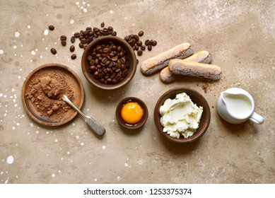Ingredients for making traditional italian cake tiramisu on a beige slate, stone or concrete background.Top view with copy space.