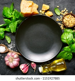 Ingredients for making traditional italian sauce pesto : basil leaves, parmesan cheese, olive oil, garlic, pine nuts and sea salt on a black slate, stone or concrete background. Top view,copy space.