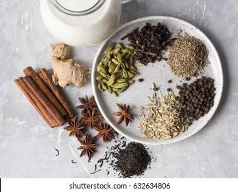Ingredients for masala tea - milk, cinnamon, cardamom, anise, fennel, ginger, black tea, star anise, black pepper, cloves on grey background. Top view