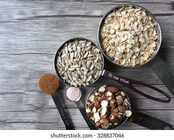 Ingredients in measuring cups and in measuring spoons; rolled oats, sunflower seeds, chopped almonds, cinnamon and himalayan salt