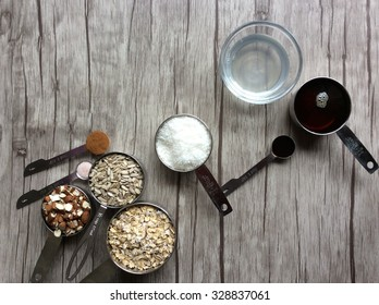 Ingredients in measuring cups and in measuring spoons; rolled oats, sunflower seeds, chopped almonds, cinnamon, himalayan salt, coconut oil, maple syrup, vanilla and shredded coconut.