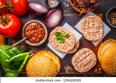 Ingredients for meat burgers with vegetables and coleslaw on a dark background, top view, copy space.
