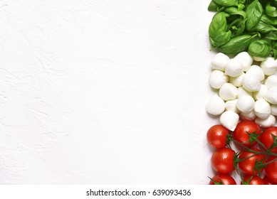 Ingredients of mediterranean cuisine in the form of the Italian flag on a white slate,stone or concrete background.Top view with copy space.
