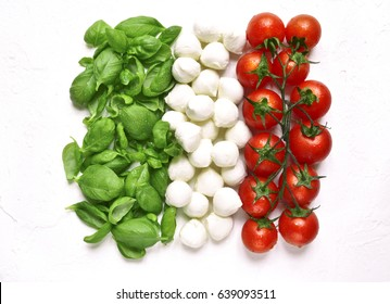 Ingredients of mediterranean cuisine in the form of the Italian flag on a white slate,stone or concrete background.Top view.