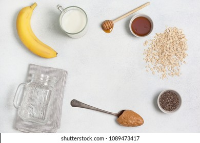ingredients for night oatmeal with bananas, chia seeds on a light concrete background. view from above. copy space