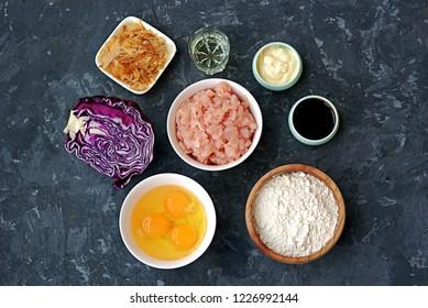 Ingredients for okonomiyaki, national Japanese dish: red cabbage, eggs, flour, mayonnaise, teriyaki sauce, sliced chicken fillet, tuna flakes, frying oil.