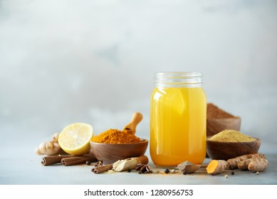 Ingredients for orange turmeric drink on grey concrete background. Lemon water with ginger, curcuma, black pepper. Vegan hot drink concept