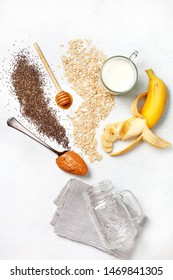 ingredients for a overnight oatmeal with bananas, chocolate drops on a light concrete background. view from above.