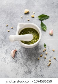 Ingredients for pesto and sauce in white mortar  made from green basil, garlic, pine nuts, Parmesan and olive oil on grey background. Preparation of Italian pesto sauce.