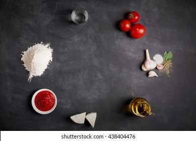 Ingredients for pizza on the chalkboard (tomatoes, cheese, sauce, water, spices, oil and flour)