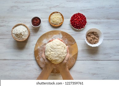 Ingredients for pizza on the table: raw dough, minced tuna, grated Parmesan and pomegranate seeds.