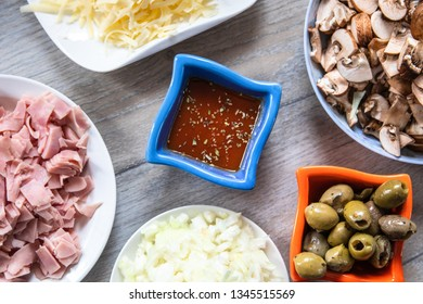 Ingredients for pizza: sliced mushrooms, ham, onion, ketchup, cheese and olives in a bowls on kitchen table