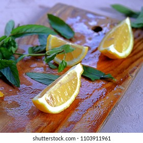 Ingredients for the preparation of lemonade, lemon wedges and mint sprigs on a wooden board. Summer concept.